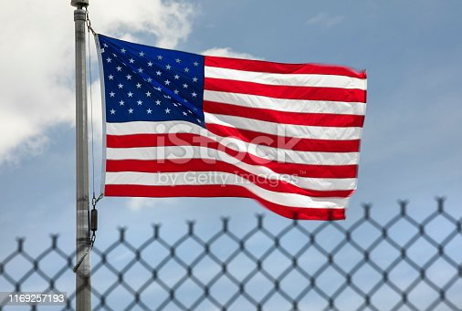 USA flags fly in the wind protected by a border protection fence