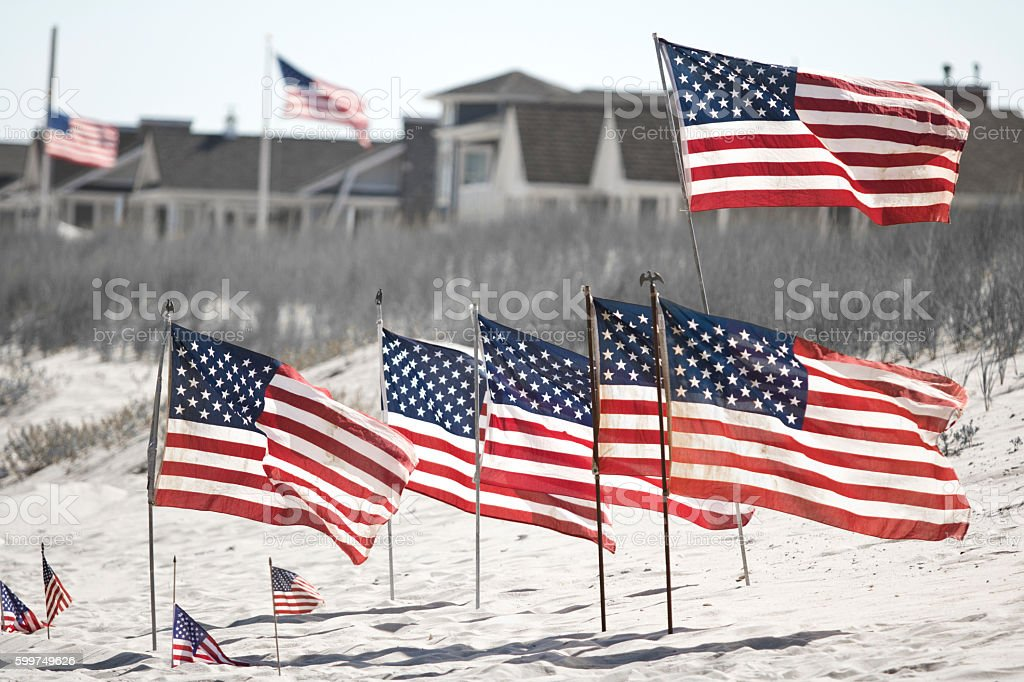 American Flags Flying At The Beach Houses In The Background