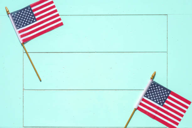 american flags on blue wood surface - patriotic background - memorial day weekend stock pictures, royalty-free photos & images