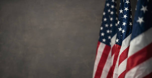 American flags over gray wal with copy space American flags over gray wall, 4th of july panoramic background with copy space american culture stock pictures, royalty-free photos & images