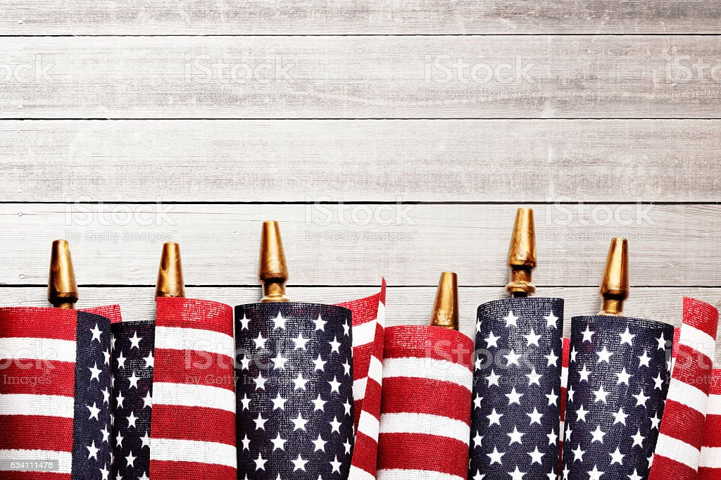 American Flags Rolled Up On Whitewashed Wooden Fence stock photo