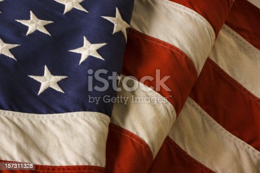 Old American flag of the United States of America, close-up. Also called Old Glory and Stars and Stripes, this banner is a patriotic decoration on Fourth of July (Independence Day), Memorial Day, Veterans Day, and other national holidays. With weathered thread embroidery stitching and faded red, white, and blue fabric.