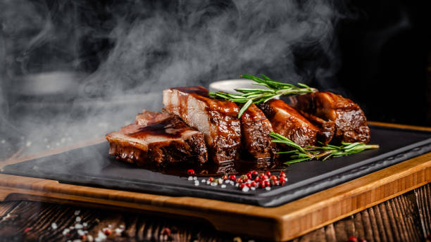 American food concept. Grilled pork ribs with grilled sauce, with smoke, spices and rosemary. Background image. copy space American food concept. Grilled pork ribs with grilled sauce, with smoke, spices and rosemary. Background image. copy space pork stock pictures, royalty-free photos & images