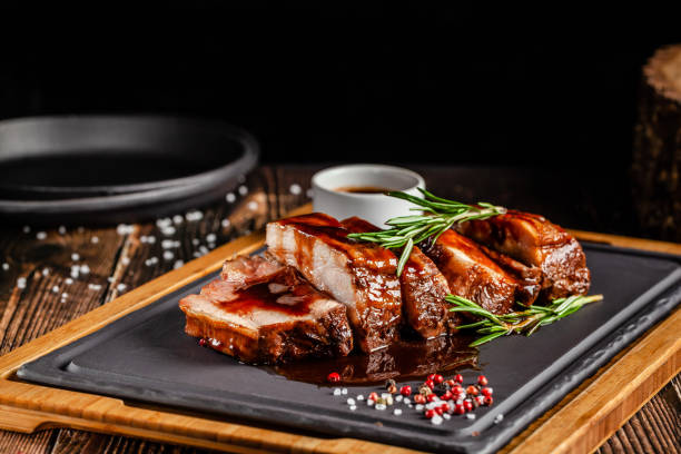 American food concept. Grilled pork ribs with grilled sauce, with smoke, spices and rosemary. Background image. copy space