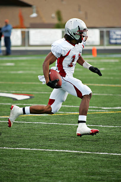 American Footbal Player in Flying Sprint after Pass Reception Wide receiver gains after catch. wide receiver athlete stock pictures, royalty-free photos & images