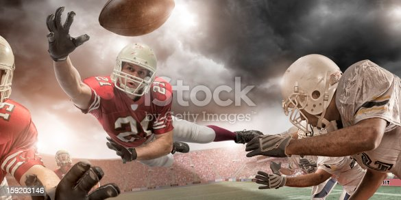 american football player in mid air about to catch ball in professional game in floodlit stadium under stormy sky at sunset