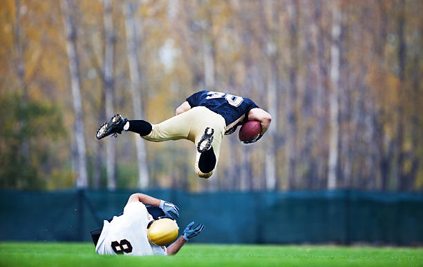 American football action. Two American football players in action. One of the players is overflying the other and scoring the touchdown.    ncaa college football stock pictures, royalty-free photos & images
