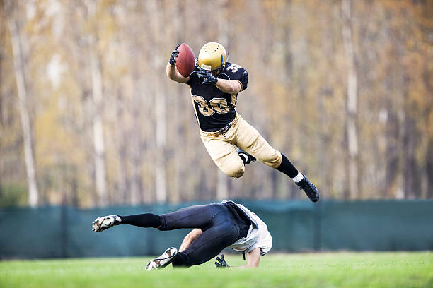 American football action. Two American football players in action. One of the players is overflying the other and scoring the touchdown.    wide receiver athlete stock pictures, royalty-free photos & images