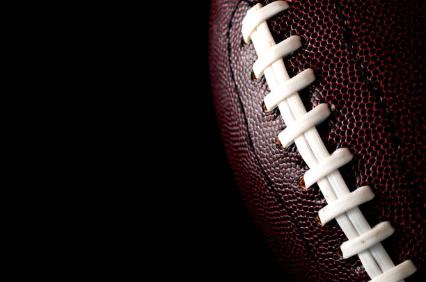 american football  and game day poster concept with close up on the texture of a ball with dramatic moody light with high contrast and copy space on a dark black background - football zdjęcia i obrazy z banku zdjęć
