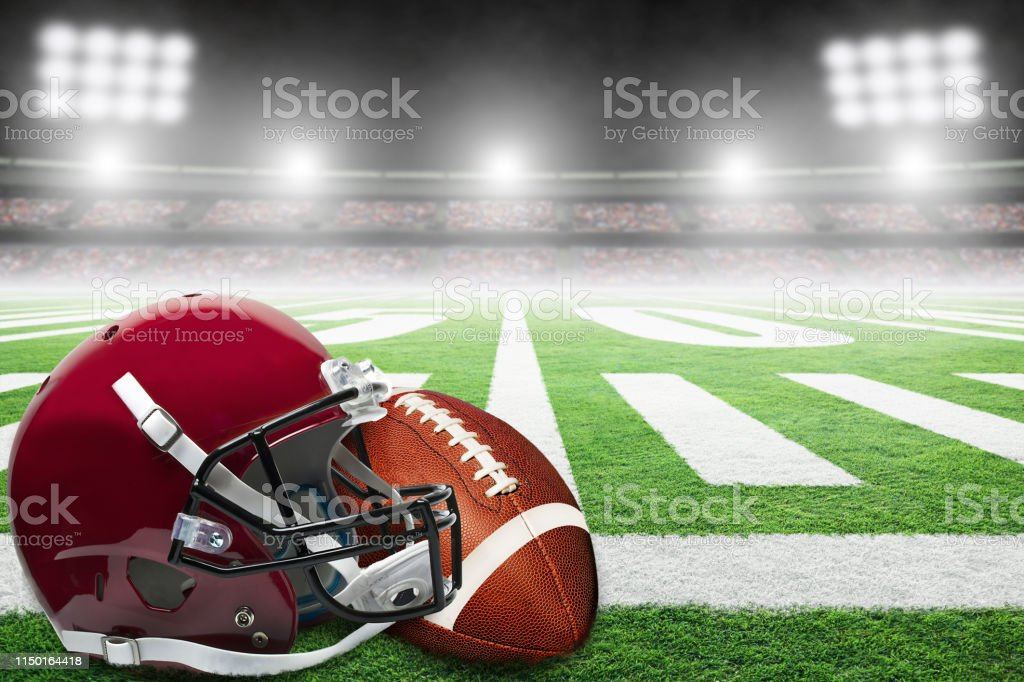 Close up of American football helmet and ball on fictitious stadium...