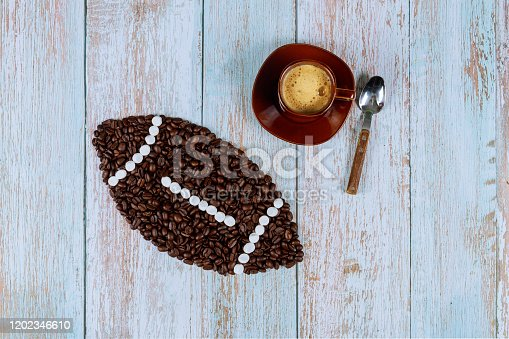 istock American football ball made from coffee beans with cup of fresh coffee. 1202346610