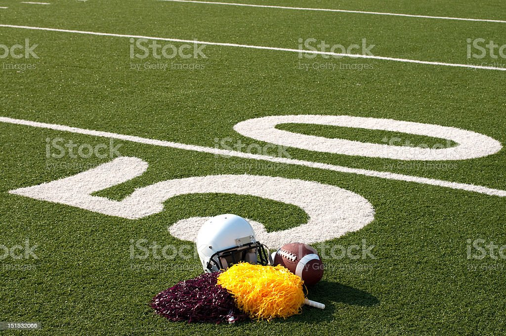 American Football Equipment and Pom Poms on Field royalty-free stock photo
