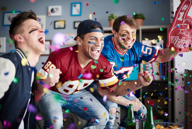 American football fans among falling confetti American football fans among falling confetti supporter stock pictures, royalty-free photos & images