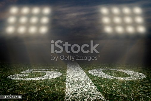 An American football field at the 50 yard line under Friday night lights