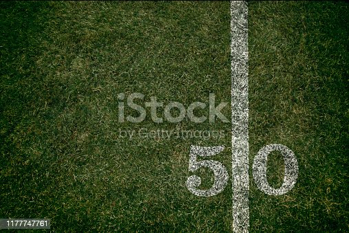 American Football field 50 yard score line. Team sports. Fifty yard line during Friday night lights.