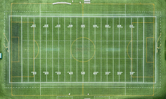 An aerial view of a full 100 yard long, marked football field shot from directly overhead from an altitude of about 1000 feet.