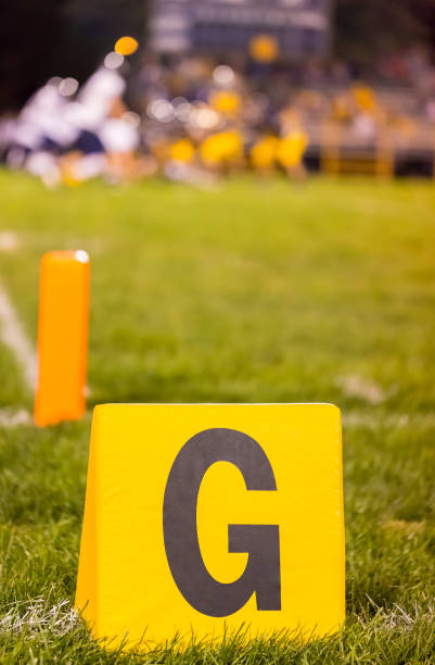 American football goal marker with blurred team Yellow american football goal line marker at school field with the student athletes on the field ncaa college football stock pictures, royalty-free photos & images