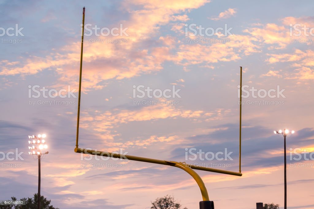 American football goal posts against sunset stock photo