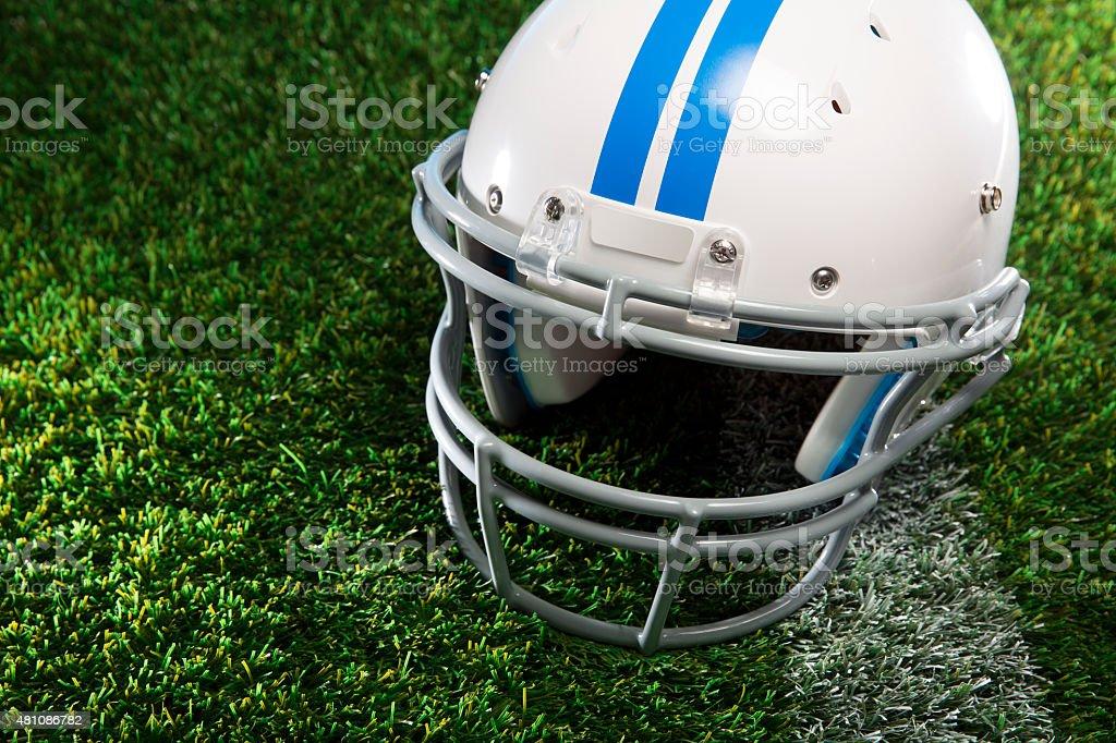 American Football Helmet on Grass Field stock photo