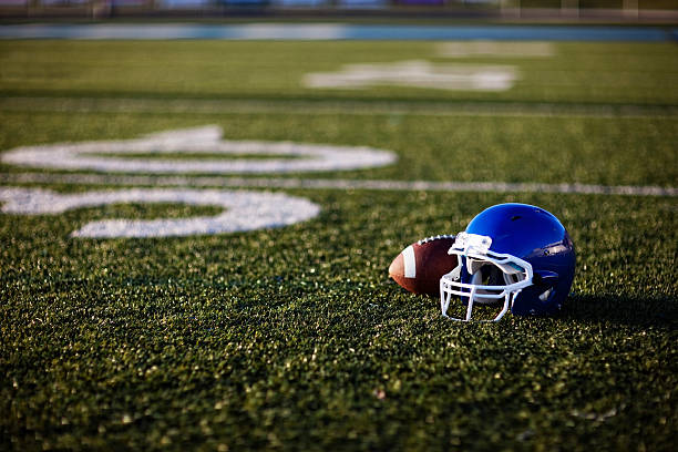 American Football Helmet An American football helmet and football on the football field. Perfect image for your football announcement. football helmet stock pictures, royalty-free photos & images