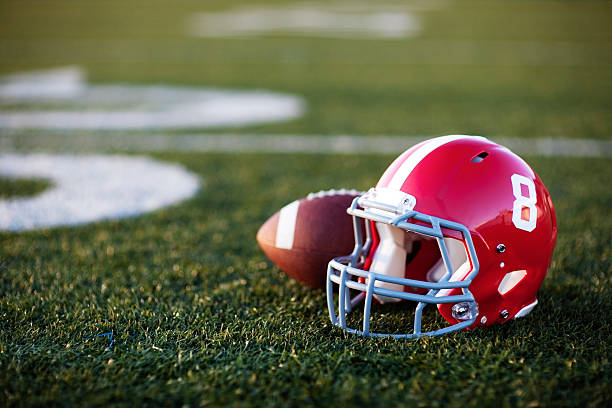 American Football Helmet A red American football helmet and football on the football field. Perfect image for your football announcement. football helmet stock pictures, royalty-free photos & images