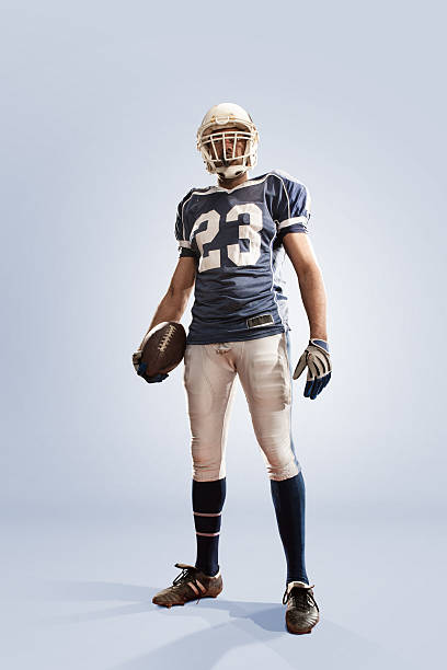 American Football Hero A low angle studio portrait of an American football player holding football, standing in heroic pose. The player is dressed in number 23 jersey– running back - and full kit including safety helmet. gloves and boots. Shot in the studio against a plain white background with copyspace. american football uniform stock pictures, royalty-free photos & images