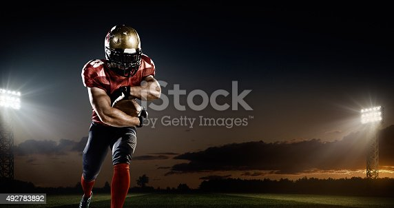 A male american football player makes a dramatic play. The panoramic view of stadium is behind him. The sky is dark and cloudy behind him.  The player is wearing generic unbranded american football uniform. The stadium is 3D rendered.