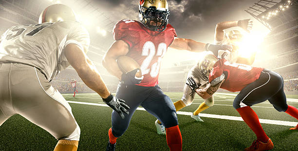 American football in action Action image of American football professional league players running with ball while matching with teammates and opposite players in outdoor floodlit stadium under sky with  sunlight. football lineman stock pictures, royalty-free photos & images