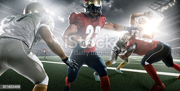 Action image of American football professional league players running with ball while matching with teammates and opposite players in outdoor floodlit stadium under sky with  sunlight.