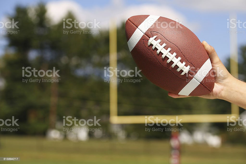 American Football in Hand over Field with Goal Post stock photo