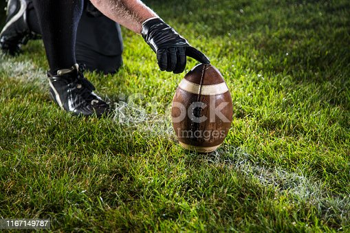 The kick. Player holding the ball in position for a kick.