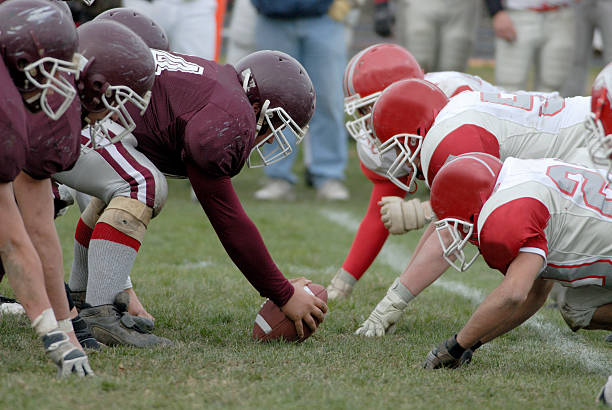 American football line of scrimmage Close up view of the line of scrimmage in a american high school football game. line of scrimmage stock pictures, royalty-free photos & images