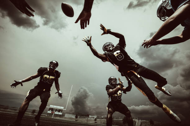 American Football Match American Football Player jumping to catch the ball under dramatic sky. ncaa college football stock pictures, royalty-free photos & images