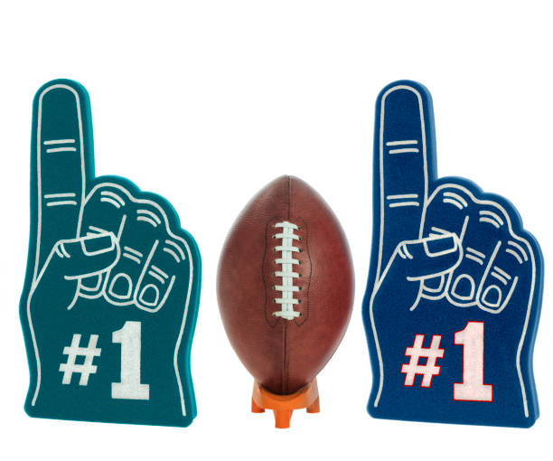 American football on a kicking tee with green and blue foam #1 finger for the BIG GAME stock photo