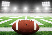 Close up of American football on stadium field with yard line markings and spotlight with blurred background and copy space. Fictitious stadium created in Photoshop.