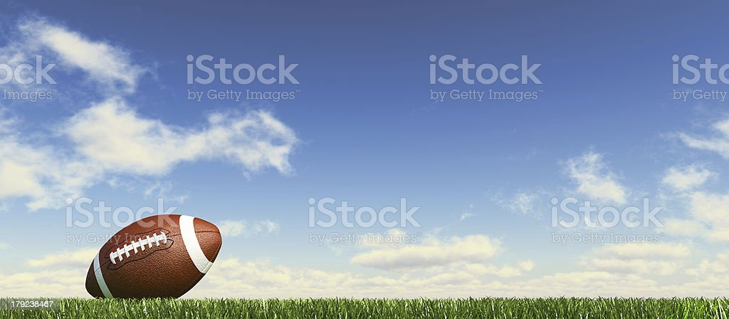 American football on grass; fluffy couds at the background. stock photo