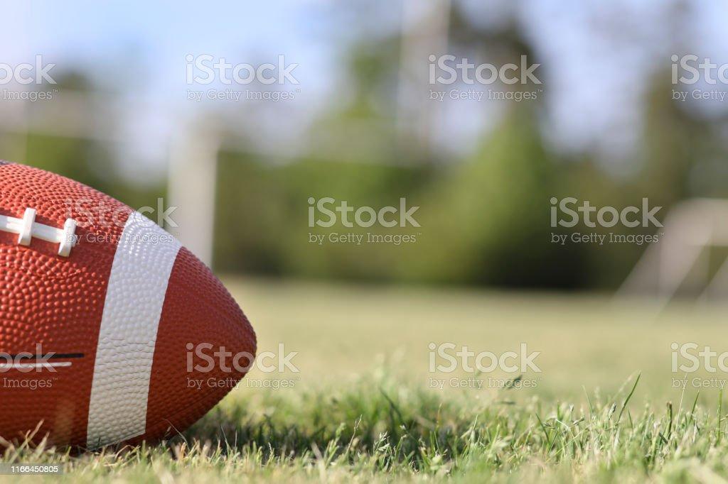 Football on grass stadium on college or high school campus. Goal...