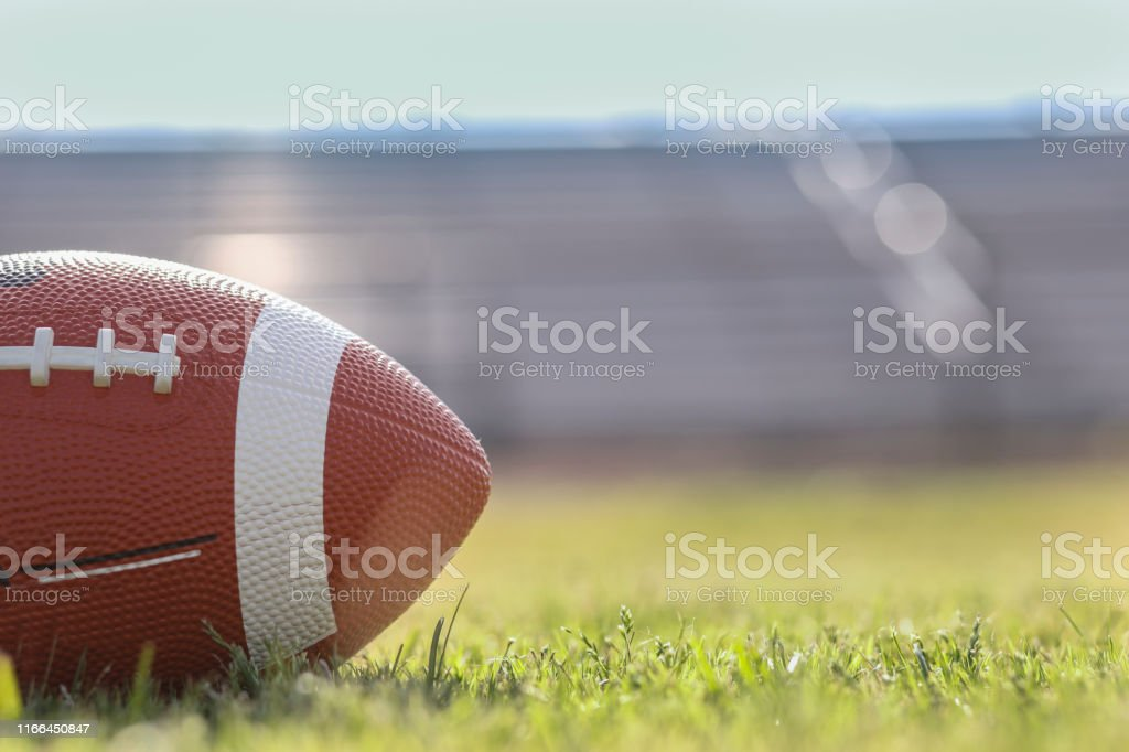 Football on grass stadium on college or high school campus. Bleachers...