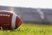 istock American football on stadium field at school campus. 1242591562