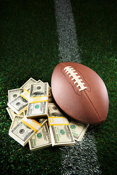 American Football Pile of Cash on Grassy Field This is a photo of an American football next to a pile of cash pertaining to fantasy football, gambling, salaries, etc safety american football player stock pictures, royalty-free photos & images
