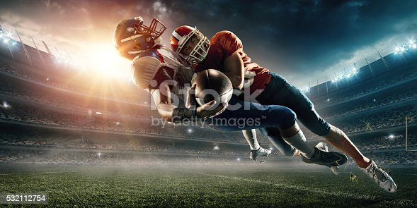 Image of an american football player being tackled by the opposite team player. All players wear unbranded professional clothes. Action takes place in a generic outdoor football stadium under a cloudy sky with bright sun.