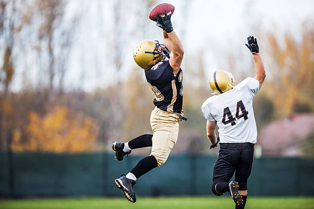 American football player catching a ball. Two American football players in action.   american football uniform stock pictures, royalty-free photos & images