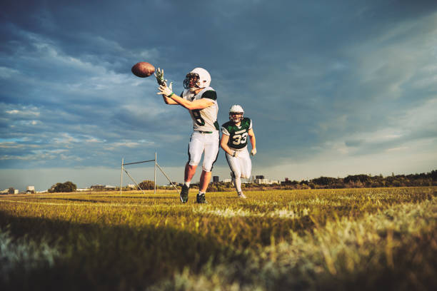 American football player catching a pass during team drills American football player receiving a pass during a team practice on a football field against a moody afternoon sky american football player stock pictures, royalty-free photos & images