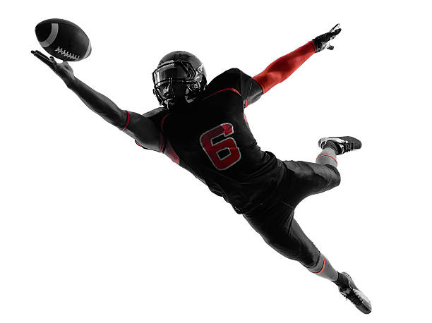 american football player catching ball silhouette one american football player catching ball in silhouette shadow on white background catching stock pictures, royalty-free photos & images