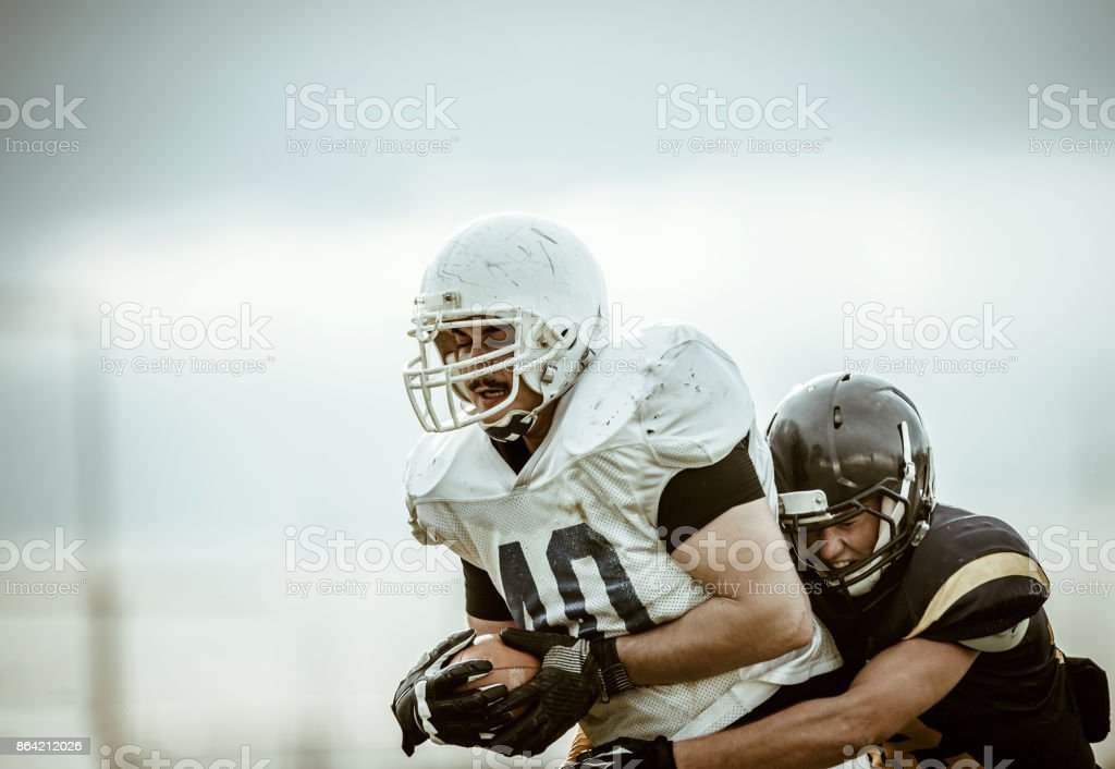 American football player catching opponent during the game. royalty-free stock photo