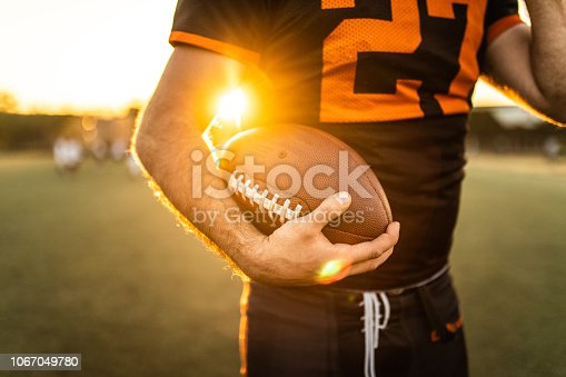 Unrecognizable American Football Player Holding Ball