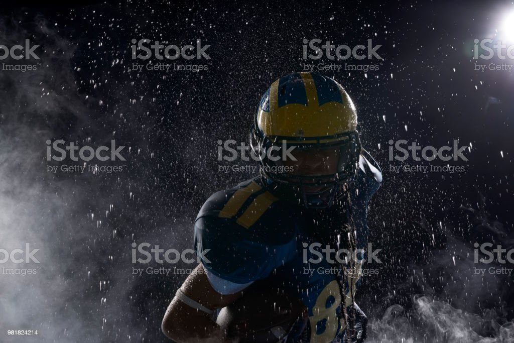 American football player in a haze and rain on black background. Portrait stock photo