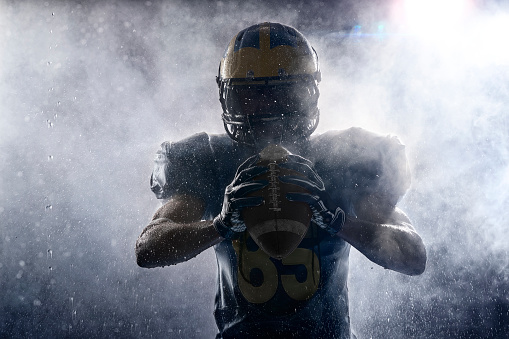 American football player in a haze and rain on black background. Portrait