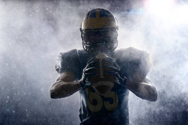 American football player in a haze and rain on black background. Portrait American football player in a haze and rain on black background. Portrait. Athlete dissecting white smoke and water drops. Sportsman shines in the rays of light quarterback stock pictures, royalty-free photos & images