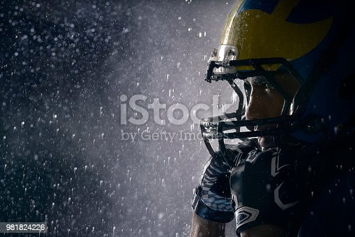 American football player in a haze and rain on black background. Portrait close-up. Athlete stands in a sport helmet under drops of water. Sportsman shines in the rays of light